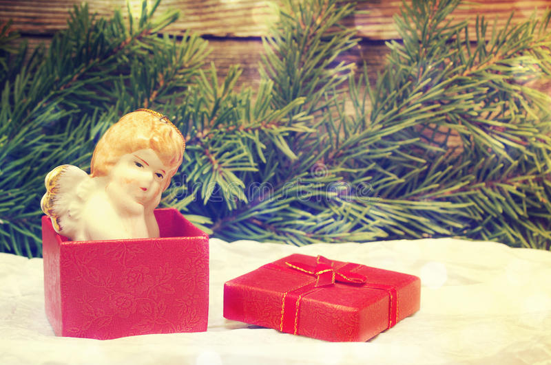 Porcelain angel in gift red packing on a wooden background. Festive background for Christmas and New year. stock images