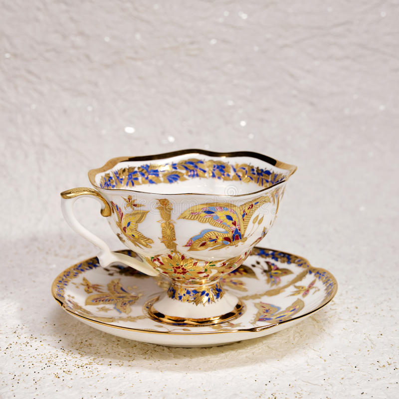Porcelain antique tea cup and saucer. Colorful decorated porcelain antique tea cup and saucer royalty free stock photos