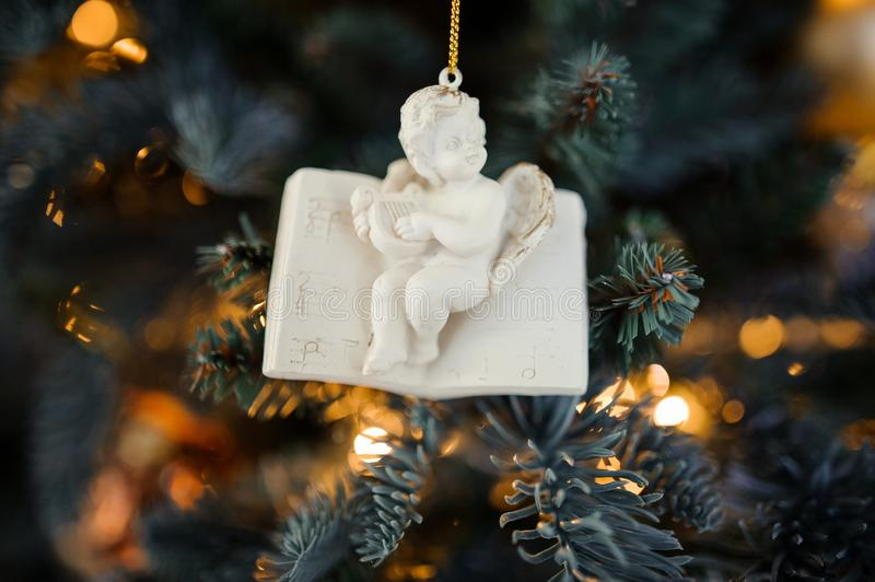 Porcelain Christmas tree decoration toy in the form of cute little angel. Sitting on the book on the background of sparkling fir tree royalty free stock images