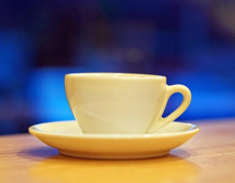 Porcelain cup. Porcelain coffee cup at table over dark blue background royalty free stock images