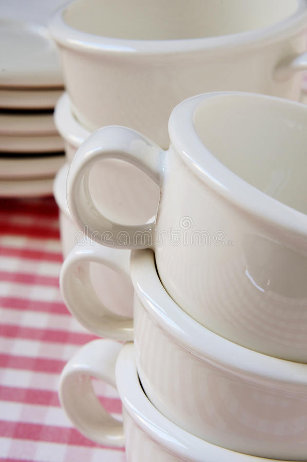 Porcelain coffee cups. A pile of empty porcelain coffee cups and plates on a checkered tablecloth royalty free stock photos
