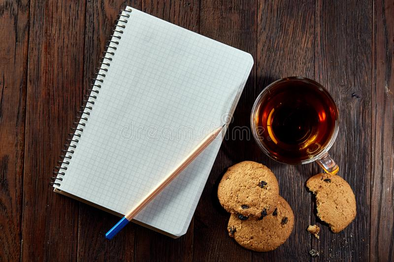 Cup of tea with cookies, workbook and a pencil on a wooden background, top view. A porcelain cup of tea with tasty chocolate chips cookies, empty workbook and stock photos