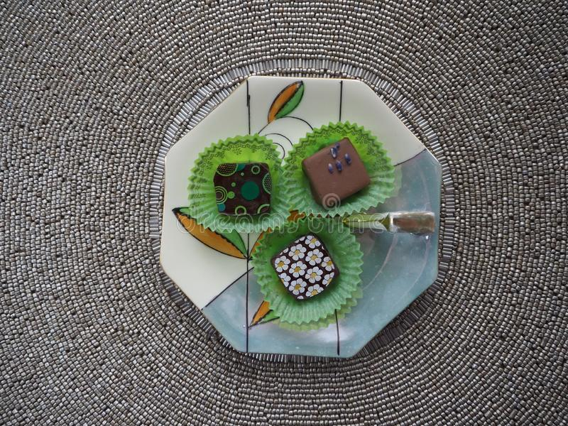Porcelain Dish With Three Chocolate Candies on Beaded Placemat. Three fancy chocolate candies in green wrappers on a porcelain dish with a beaded place mat in stock photo
