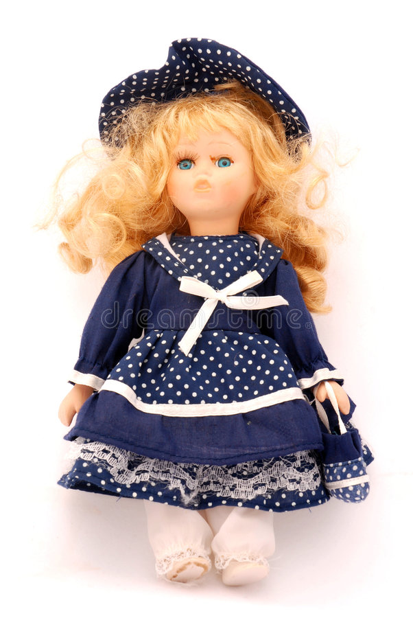 Porcelain doll. An old toy for female kids, a vintage porcelain doll in a blue dress. Image isolated on white studio background royalty free stock images