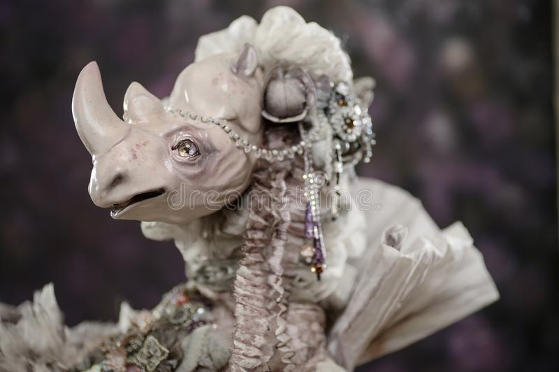 Porcelain doll white rhino victorian vintage old. Porcelain clay statuette doll animal doll white rhino woman dress silk pearl victorian& Beauty handmade stock image