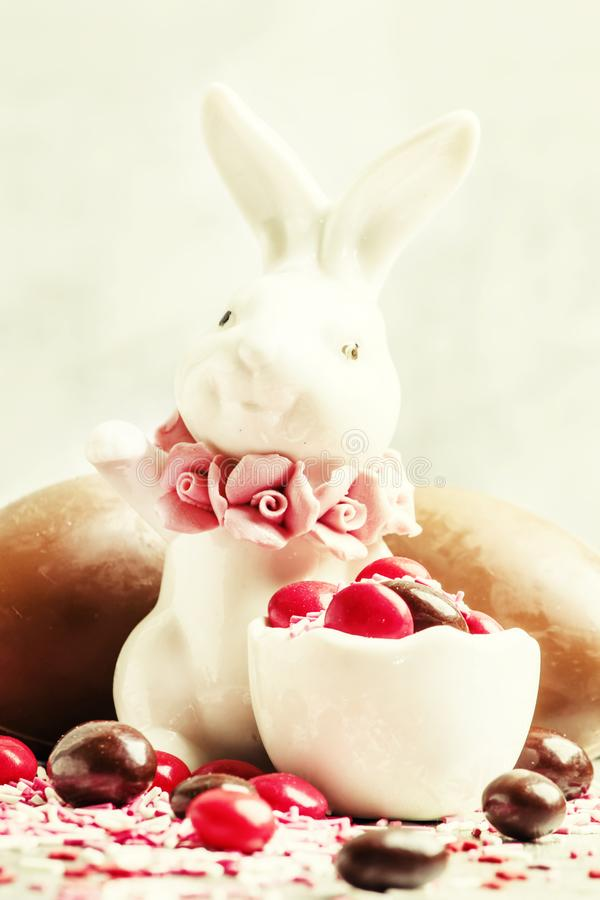 Porcelain Easter bunny with brown and red chocolate eggs and col stock photos