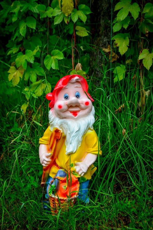 Porcelain figurine dwarf. Summer porcelain figurine dwarf under the open sky stock photos