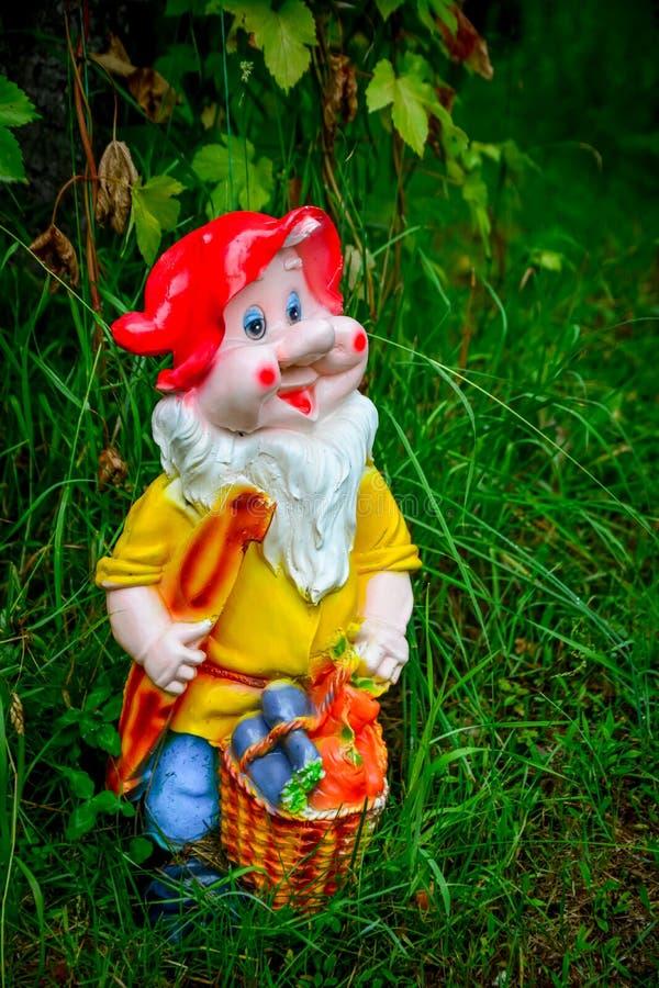 Porcelain figurine dwarf. Summer porcelain figurine dwarf under the open sky stock images