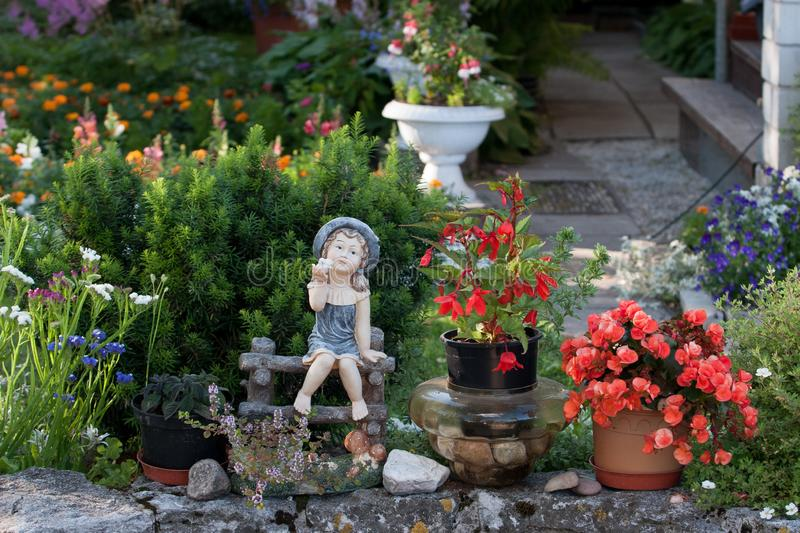 Porcelain garden figurine toy girl sitting in the garden on a bench barefoot. stock photos