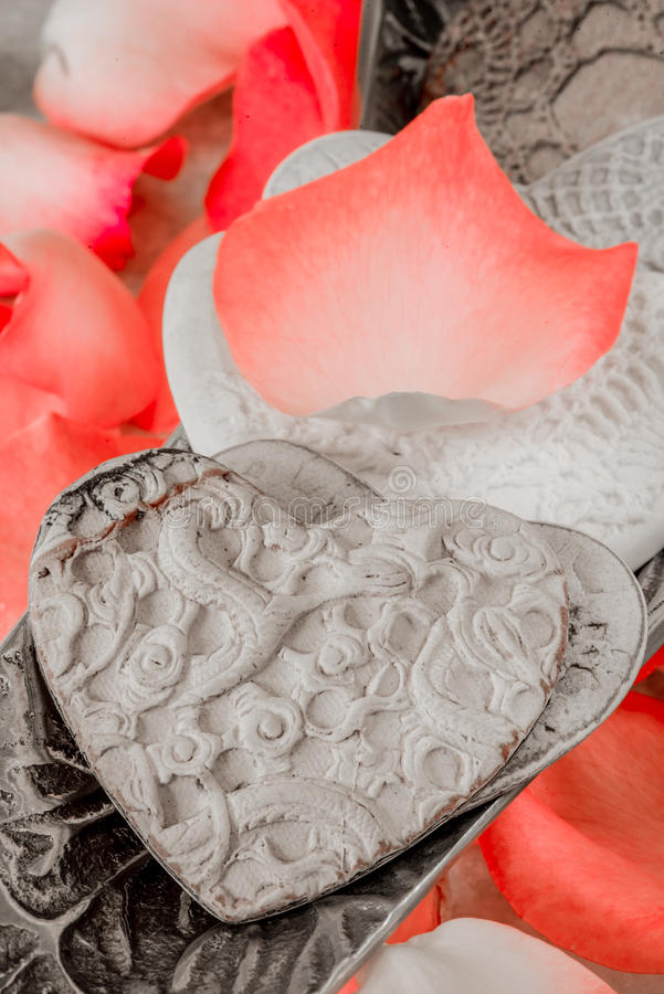 Porcelain Hearts and Rose Peddles. Pocelain hearts in a silver bowl together with light red rose peddles royalty free stock images