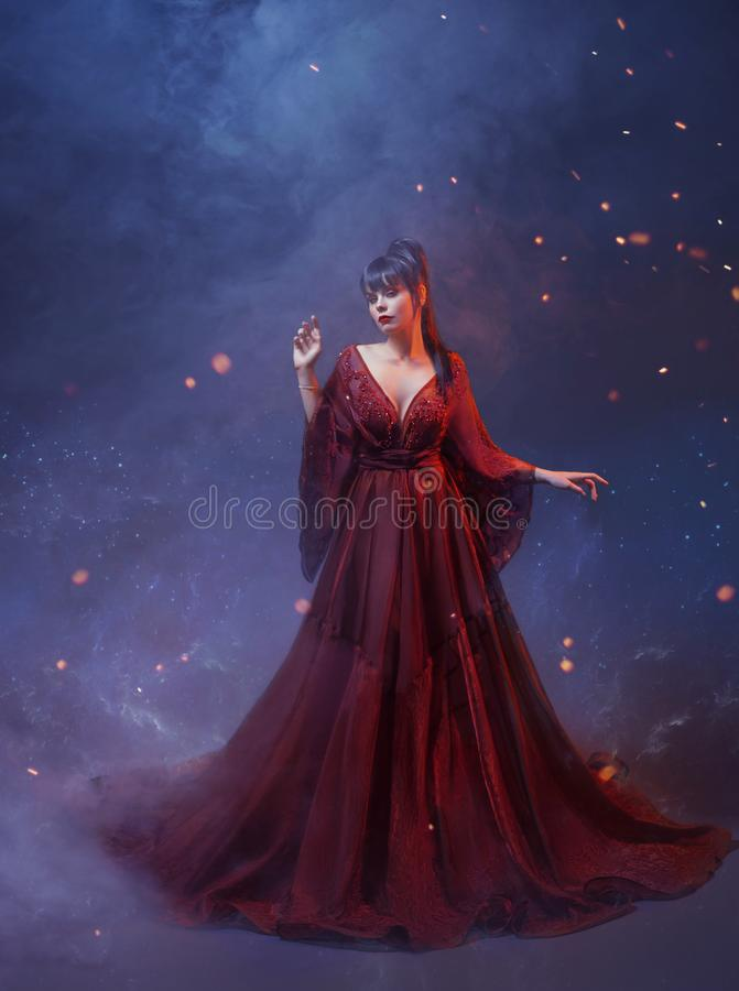 A porcelain princess with blue long hair is dressed in a gentle long maroon light dress with open shoulders and free. Sleeves, standing in a blue fog and sparks royalty free stock photo
