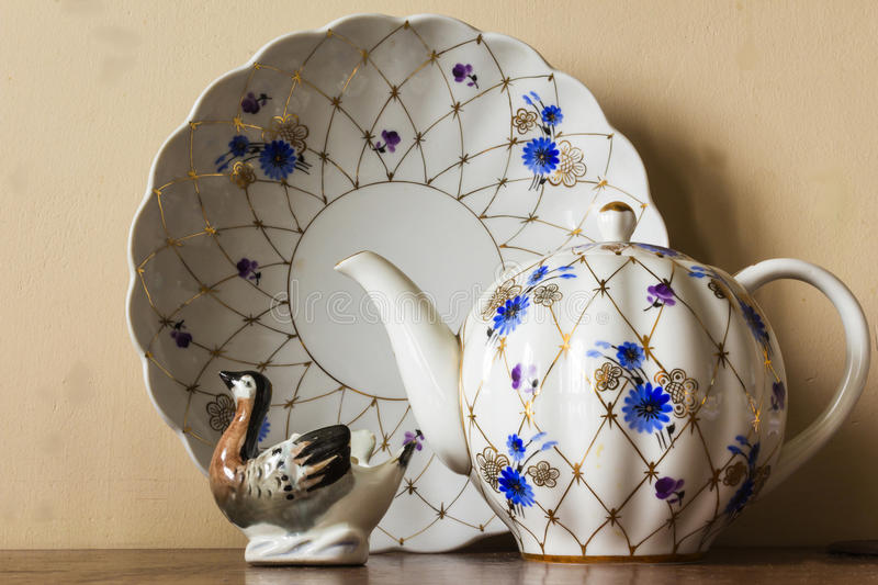 Porcelain sugar bowl, cup, milk, dish with golden pattern and blue flowers. royalty free stock photos