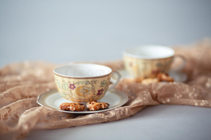 Porcelain tea cups with biscuits. Two porcelain tea cups with biscuits royalty free stock photos