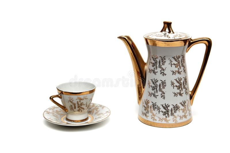Porcelain tea utensils with a beautiful pattern. Porcelain teapot with beautiful pattern with saucer and cup on white background royalty free stock images