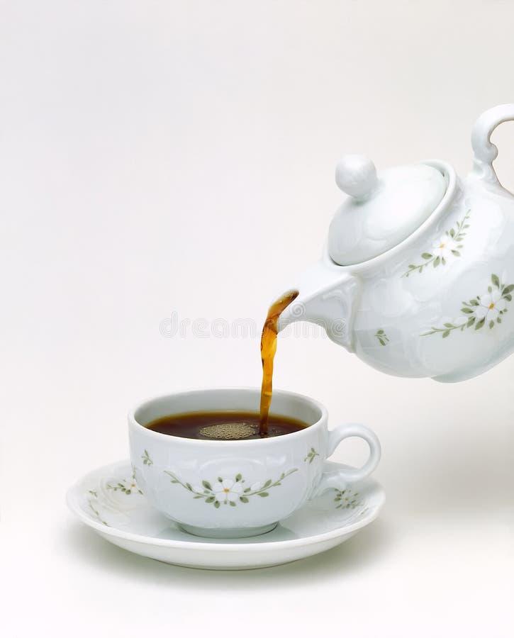 Porcelain teapot pouring tea royalty free stock photos