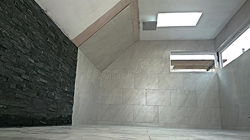 Porcelain tiling woodfall tiles split face style. A bathroom tiling photograph floor and walls with fitted bathroom furniture. Contemporary clean finish to high stock photo