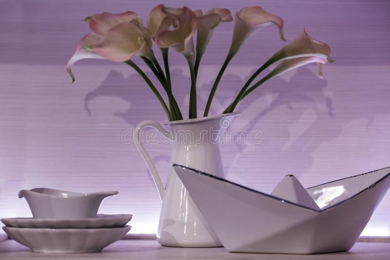 a porcelana de jantar branca ajustou-se com pires com um jarro de flores, de molheira, e de uma bacia de salada de forma incomum, fotos de stock