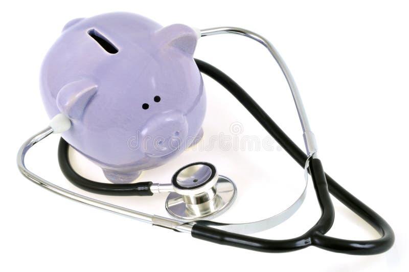 Porcellino salvadanaio circondato da uno stetoscopio su un fondo bianco immagine stock libera da diritti