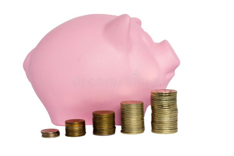 Porcellino salvadanaio del maiale e pile rosa di monete del metallo fotografia stock