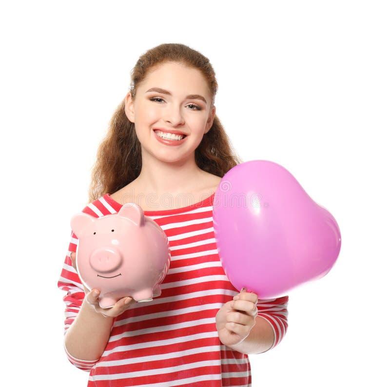 Porcellino salvadanaio della tenuta della giovane donna e pallone a forma di del cuore su fondo bianco Concetto di risparmio dei  immagini stock libere da diritti