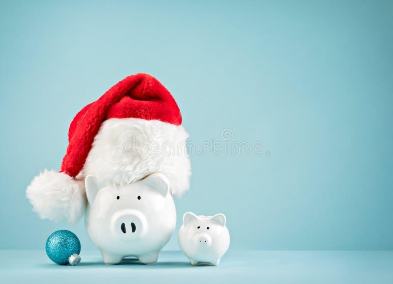 Porcellino salvadanaio di finanze di Natale che porta il cappello di Santa immagine stock libera da diritti