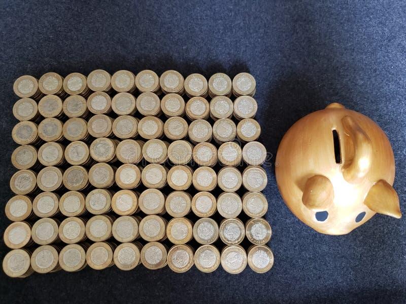 porcellino salvadanaio dorato del maiale e monete impilate dei pesi messicani fotografia stock libera da diritti