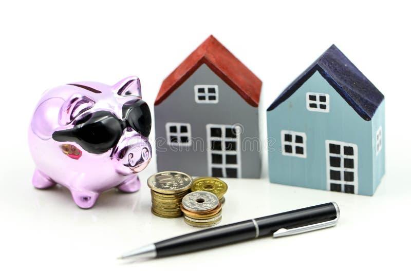 Porcellino salvadanaio e casa del modello con soldi, monete, risparmio per il est reale immagine stock libera da diritti