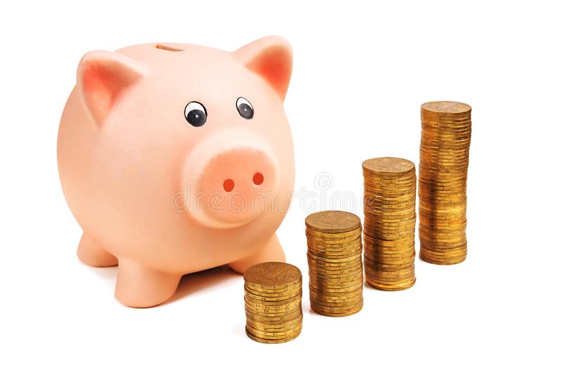 Porcellino salvadanaio e punti della moneta su bianco immagini stock