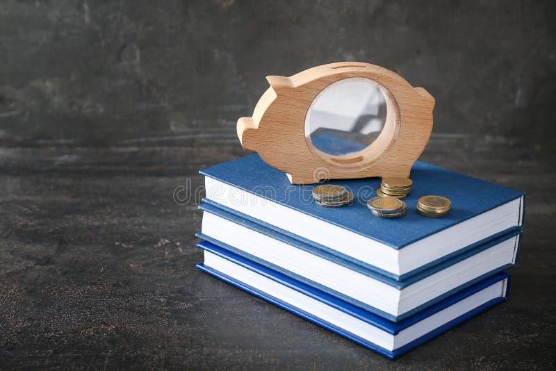 Porcellino salvadanaio, monete e pila di libri sulla tavola Concetto del risparmio per istruzione fotografia stock