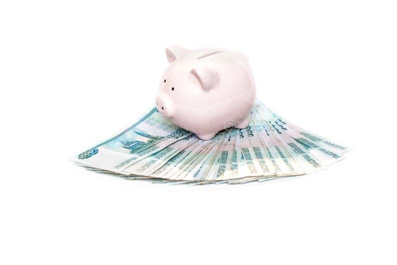 Porcellino salvadanaio rosa con una banconota in una pianificazione finanziaria, nel risparmio e nel concetto di investimento sop fotografie stock