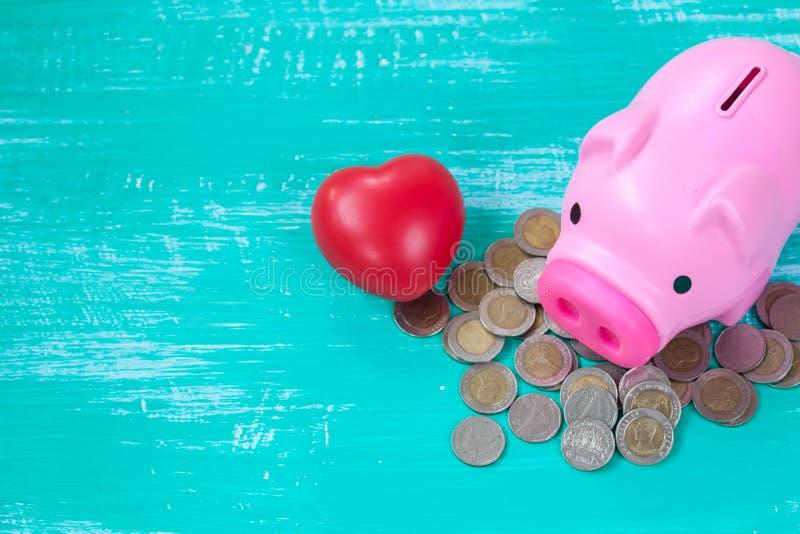 porcellino salvadanaio rosa sopra la pila delle monete, soldi di risparmio immagine stock
