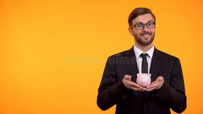 Porcellino salvadanaio sorridente della tenuta dell'uomo di affari, concetto di risparmio dei soldi, fondo arancio fotografia stock libera da diritti