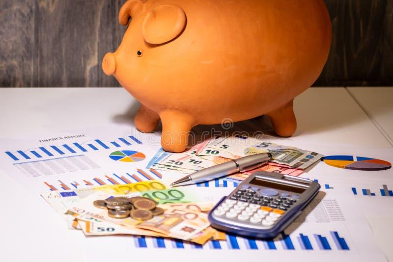 Porcellino salvadanaio su soldi, sulle fatture degli euro, sulle relazioni di attività, sulla penna e sul calcolatore fotografia stock libera da diritti
