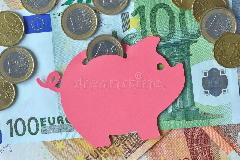 Porcellino salvadanaio sulle euro banconote e monete - concetto di risparmio dei soldi immagine stock libera da diritti