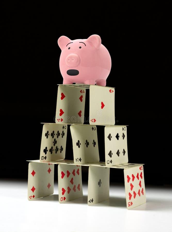 Porcellino salvadanaio turbato che sta sul castello di carte vacillante fragile con un fondo scuro immagini stock libere da diritti