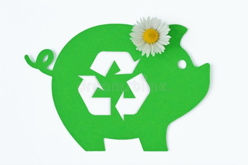 Porcellino salvadanaio verde di carta con il riciclaggio simbolo e del fiore della margherita su fondo bianco - concetto di soldi immagine stock libera da diritti