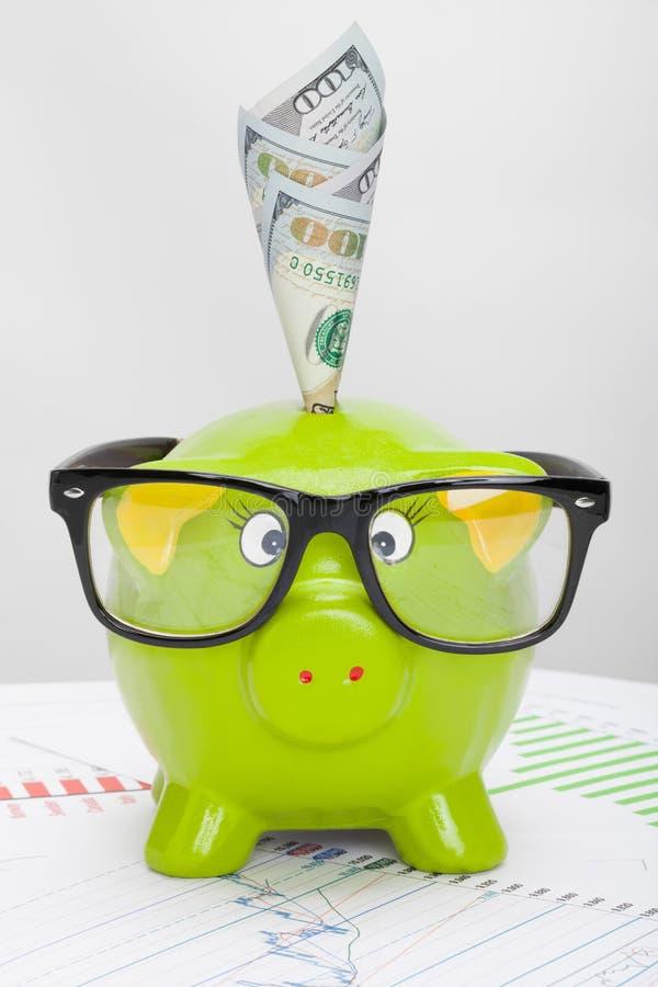Porcellino salvadanaio verde sopra il grafico del mercato azionario con 100 dollari di banconota immagine stock