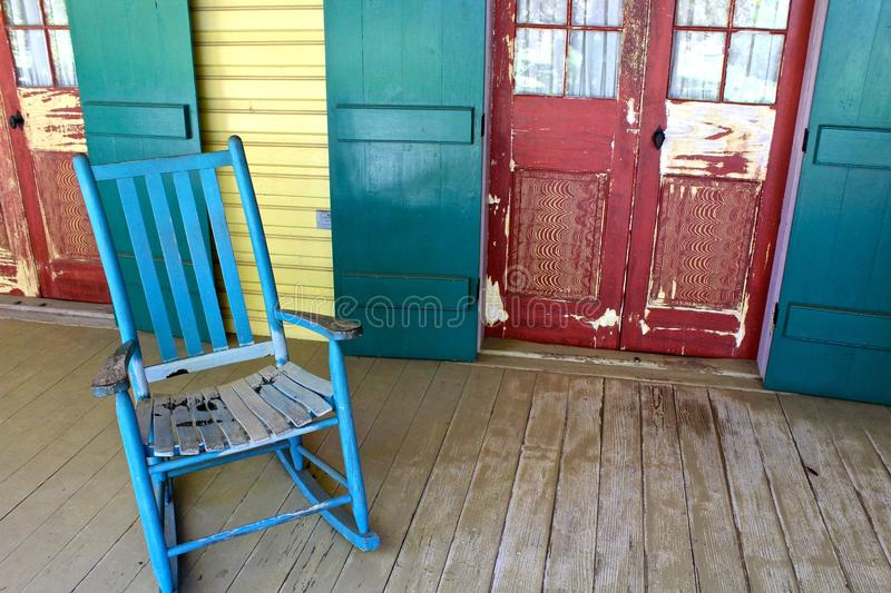 Porch Chair. An old blue porch chair on a wooden veranda with red door on a Louisiana plantation stock image