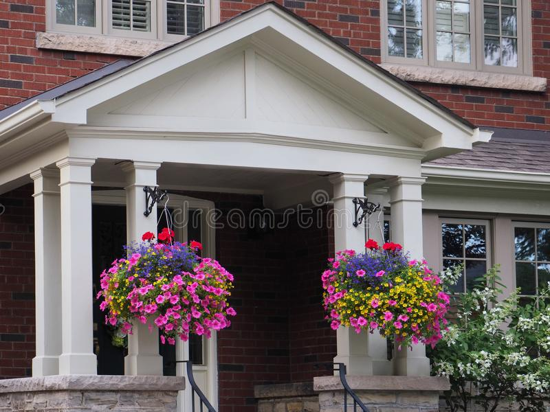 Porch with hanging baskets of flowers royalty free stock photography