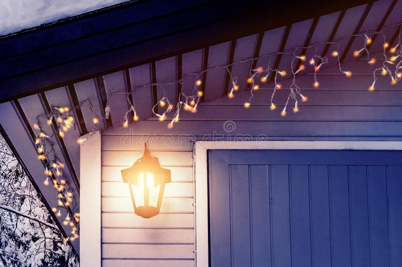 Porch of the house is decorated in the traditional Scandinavian style with a lantern and Christmas lights - concept of home warmth stock photos