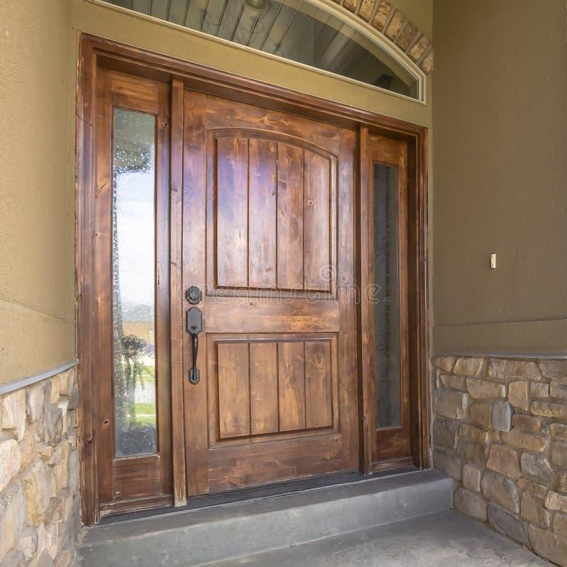 Porch inicial da armação quadrada e porta da frente da madeira marrom com vistas laterais e janela de trânsito arquitetada foto de stock