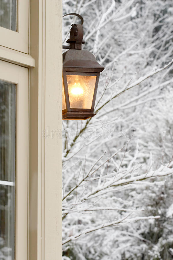 Porch light snowy house royalty free stock photography