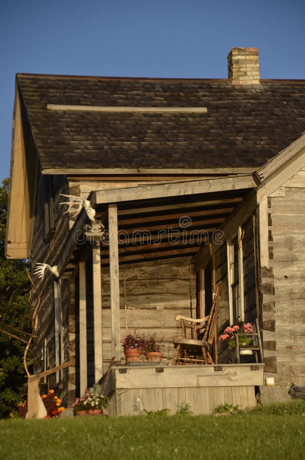 Porch of a log cabin. A large log cabin built to mimic buildings of the past has a porch with a overhang decorated with relics of the past stock photo