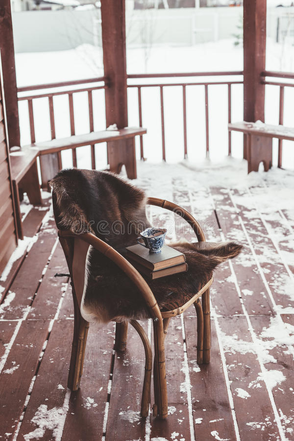 Porch of log cabine with snow. Chair with fur cover on a porch deck of a log cabin with snow, cold winter relax weekend royalty free stock photography