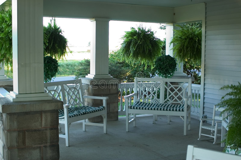 Porch View. A view of a porch with sitting area shaded by a roof supported by columns. Porch is on an old farm house in Northern Ohio royalty free stock photography