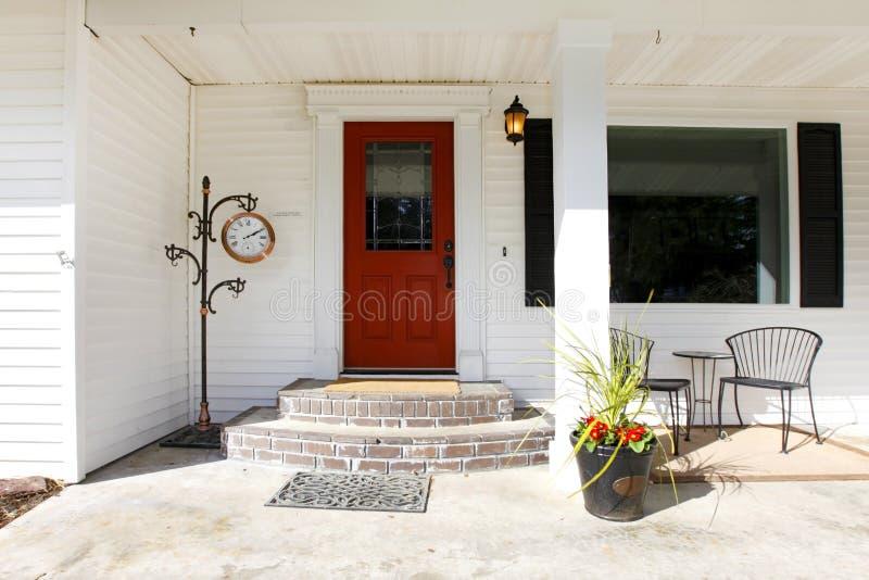 Porche classique blanc avec une porte en bois rouge image libre de droits
