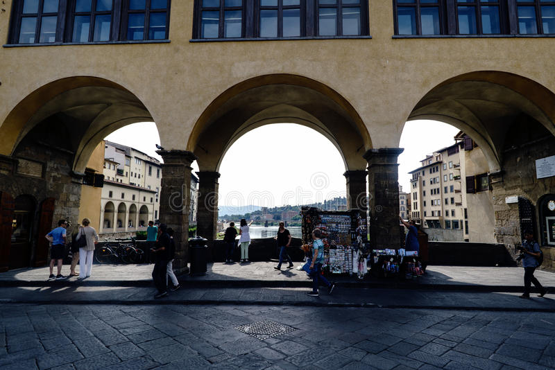 Porches on one side of the bridge over the river Arno, called `Ponte Vecchio` with people walking royalty free stock image
