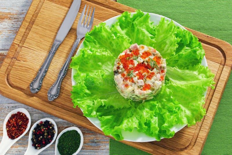 Porción de ensalada más olivier con el caviar rojo en la placa blanca fotografía de archivo libre de regalías