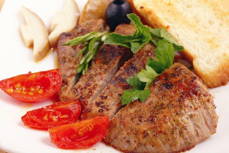 Porción de la carne con las verduras en una placa del fondo blanco fotografía de archivo libre de regalías