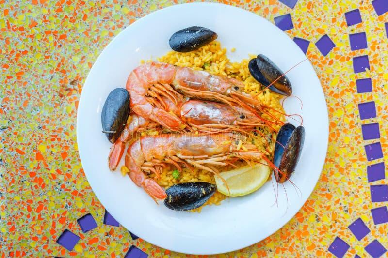 Porción de la paella, arroz con los camarones del tigre, mejillones y limón foto de archivo